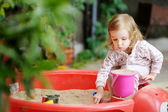 Little girl playing in a sandbox — Stock Photo