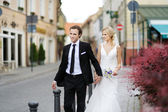 Bride and groom walking in a town — Stok fotoğraf