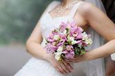 Bride holding pink wedding flowers bouquet — Stock Photo