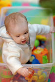 Pretty little girl in a toy box — Stock Photo