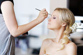 Young beautiful bride applying wedding make-up — Stock Photo