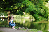 Adorable girl sitting by the water — Stock Photo