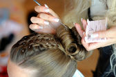 Woman's hands making a hairstyle — Stock Photo