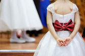 Beautiful bow on flower-girl's dress — Stock Photo