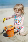 Cute little girl playing on a beach — Stock Photo