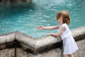 Funny child having fun by a city fountain — Stock Photo