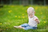 Dziecko siedzi na zielonej trawie — Zdjęcie stockowe