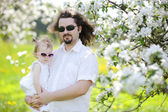 Young father and his daughter in blossoming trees — Stock Photo