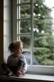 Adorable toddler girl looking at raindrops — Stock Photo