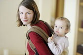 Young mother and her girl in a baby carrier — Stock Photo