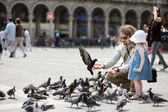 Adorable little girl and her father feeding pigeons — Stock Photo