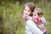 A girl having a piggyback ride on her mom — ストック写真
