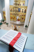 Orthodox Holy Bible on the table agains the sanctuary — Stock Photo