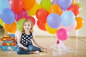 Little birthday girl with tons of balloons — Stock Photo