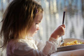 Cute little girl eating pasta — Stock Photo
