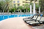 Ombrelloni bianchi in una piscina tropicale resort — Foto Stock