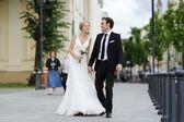 Bruden och brudgummen promenader i en stad — Stockfoto