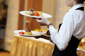 Waitress carrying three plates with meat dish — Stock Photo