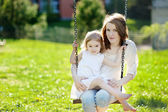 Mother and daughter on garden swing — Stock Photo