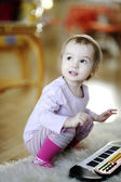 Little girl playing toy piano — Stock Photo