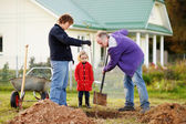 Little girl and her grandparents planting a tree — Stock Photo