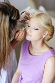 Young beautiful bride applying wedding make-up — Stok fotoğraf