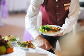 Waiter carrying a plate — Stock Photo