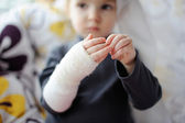 Little girl showing her bandaged hand — Stock Photo