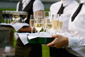 Waitress with dish of champagne glasses — Stock Photo