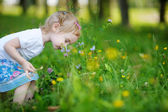 Adorable little girl sniffing flowers outdoors — Stock Photo