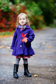 Little girl in bright blue coat at autumn — Stock Photo