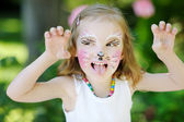 Adorable little girl with her face painted — Stock Photo