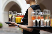 Waiter with dish of wine and juice glasses — Stock Photo