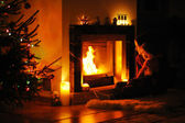 Young mother and daughter by a fireplace — Stock Photo