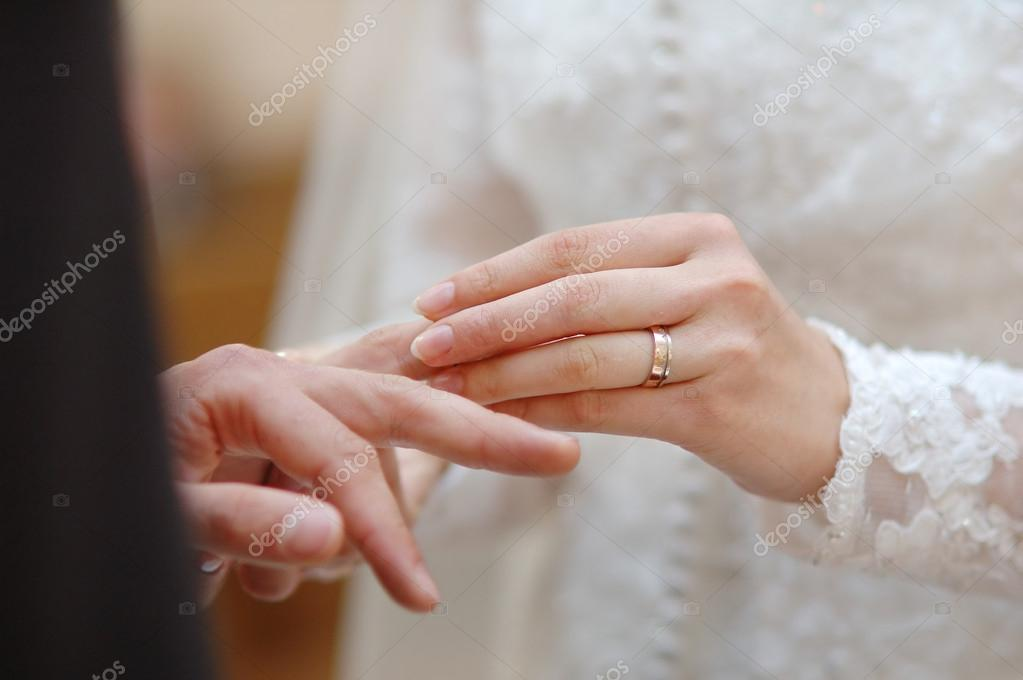 Bride putting a wedding ring on groom's finger  Stock Photo #13725721