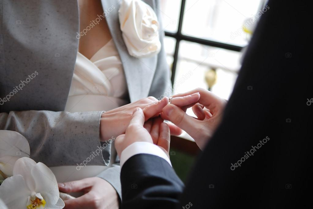 Groom putting a wedding ring on bride's finger — Stock Photo #13726076