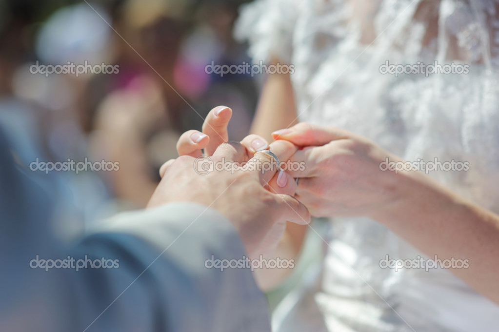 Bride putting a wedding ring on groom's finger — Stock Photo #13726290