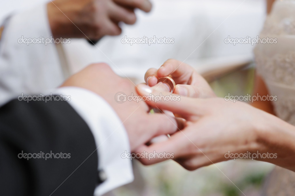 Bride putting a wedding ring on groom's finger — Stock Photo #13726306