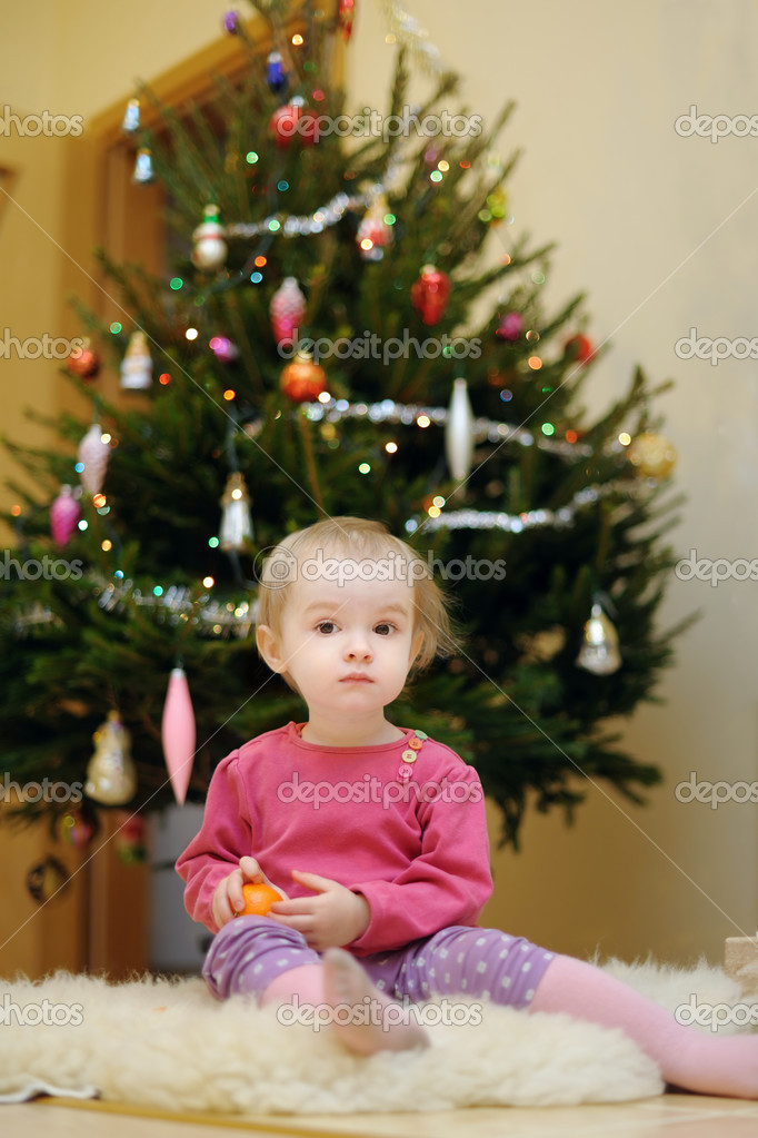 Adorable toddler girl sitting under the Christmas tree  Stock Photo #13727081