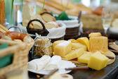 Formaggi freschi e pane su un tavolo — Foto Stock