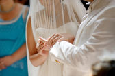 Bride putting the ring on groom's finger — Stock Photo