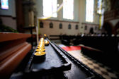 Row of small candles and at church — Stockfoto