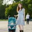 Mother on roller skates with baby stroller — Stock Photo