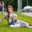Young mother on roller skates with her baby — Stock Photo