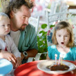 Little girl blowing out candles in her birthday — Stock Photo #43455497
