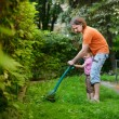 Father and a child cutting the grass — Stock Photo