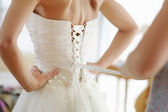 Helping the bride to put her wedding dress — Stock Photo