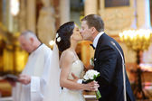 Bride and groom kissing in a church — Stock Photo