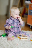 Cheerful child playing with wooden toys — Stock Photo