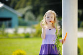 Adorable little girl with carrots — Stock Photo